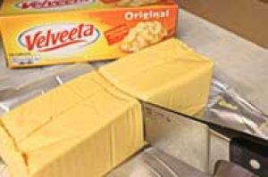 block of velveeta cheese with a knife through the middle
