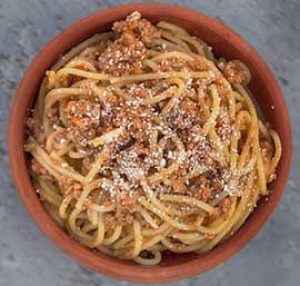 bowl of spaghetti with tomato sauce and grated parmesan