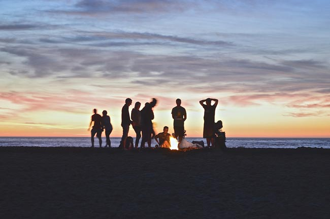 campfire on beach with group of people