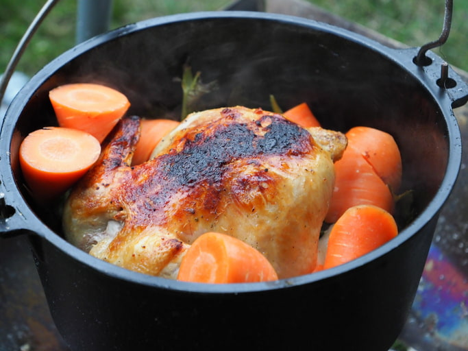 dutch oven for camping with chicken and carrots over a campfire