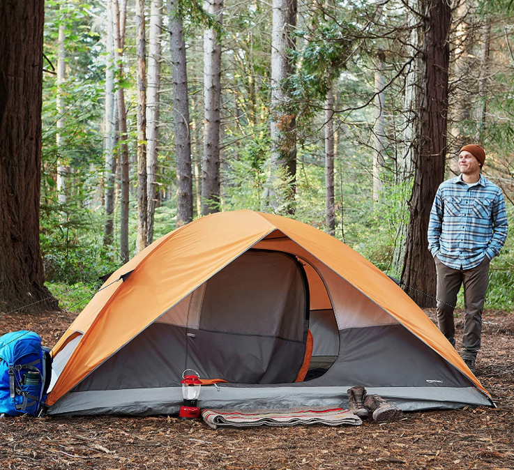 man standing outside waterproof tent for camping in the rain