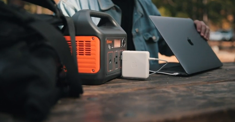 portable power station charging a laptop for campers on an outdoor table
