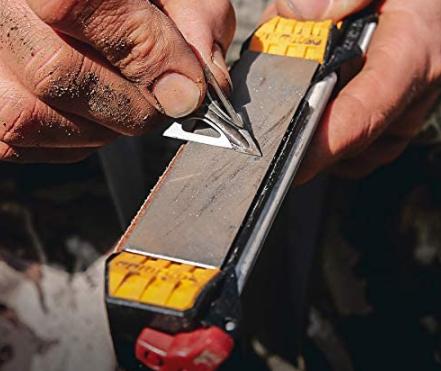 Camper sharpening a blade on a knife sharpener