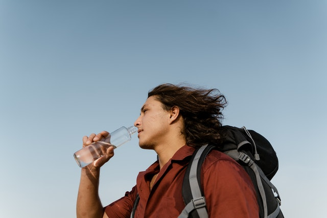 camper drinking water from a water bottle